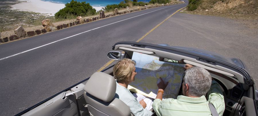 Photo of a senior couple driving in a comfortable by the ocean,  looking at a map.